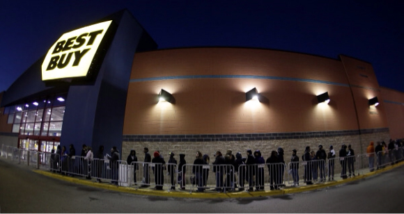 Shoppers wait for a Best Buy to open Thursday, Nov. 28, 2013, in Overland Park, Kan. Instead of waiting for Black Friday, which is typically the year's biggest shopping day, more than a dozen major retailers are opening on Thanksgiving this year. (AP Photo/Charlie Riedel)